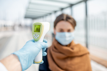 Obraz Measuring temperature with infrared thermometer of a young woman in face mask at a checkpoint during an epidemic outdoors. Concept of prevention the spread of the virus - fototapety do salonu