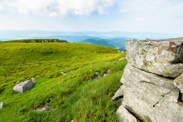 beautiful summer landscape in mountains. green grassy meadow on the hill side. view in to the distant range beneath a blue sky with clouds