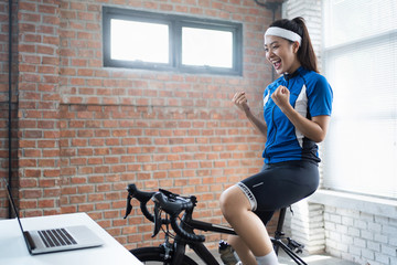 Asian woman cyclist. She is exercising in the house. By cycling on the trainer And playing online...