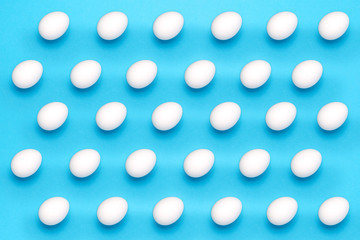 White eggs in a abstract pattern on blue background