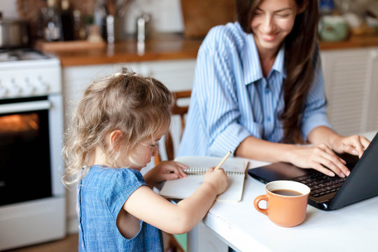 Working mom works from home office with kid. Happy woman using laptop. Cute child drawing in mother notebook. Freelancer workplace at kitchen table. Female business, career. Lifestyle family moment.