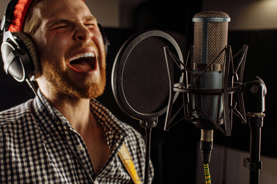 young caucasian man emotionally practice singing before music performance, concert on stage. handsome guy warms up the vocal cords in recording studio