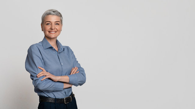 Portrait Of Mature Businesswoman Posing With Folded Arms Over Light Background