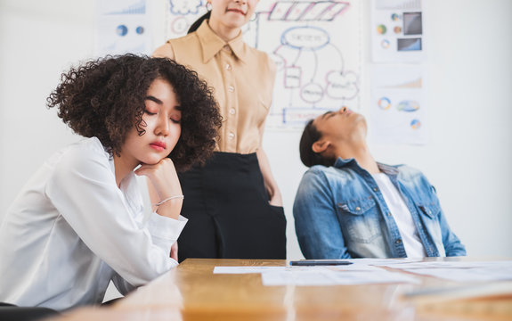 Asian business people feel bored and tired/exhausted/sleepy while working in office