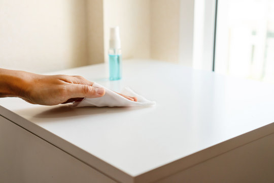 Woman hand cleaning headboard with disinfectant wet wipe and alcohol spray in bedroom at home. Concept of disinfecting surfaces from bacteria or viruses. Close up