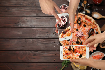 Food bloggers taking pictures of delicious seafood pizza at wooden table, closeup. Space for text