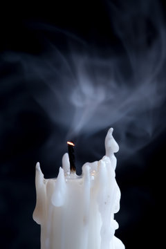 moke coming off the wick of a white candle against a dark background