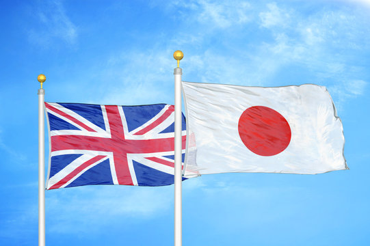 United Kingdom and Japan two flags on flagpoles and blue cloudy sky