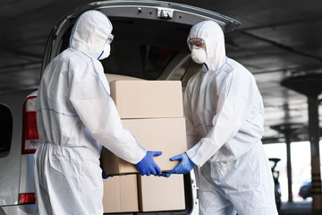 Workers in coronavirus hazmat suits delivering drugs Wall mural