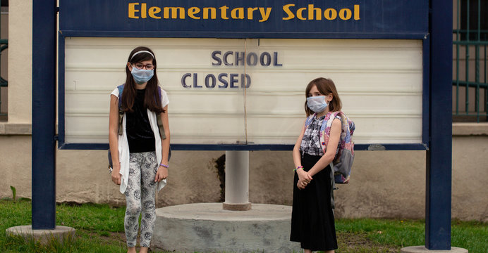 Two school aged girls are standing in front of their closed school with facemasks on during the outbreak of covid-19.