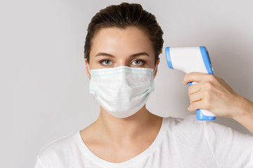 Young woman wearing face mask is measuring body temperature