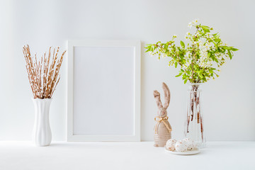 Home interior with easter decor. Mockup with a white frame and spring flowers in a vases on a light background