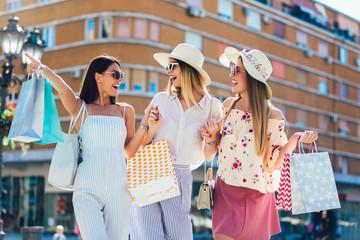Beautiful women with shopping bags having fun. Wall mural