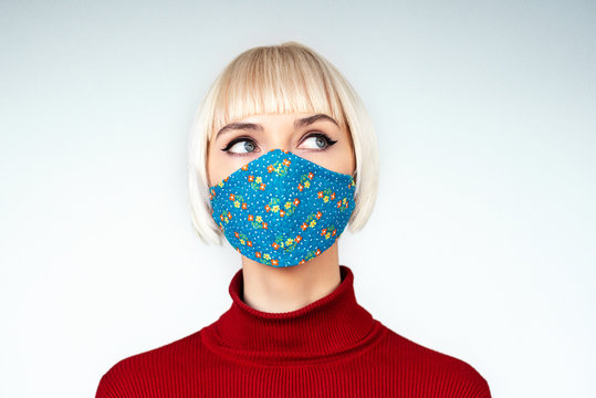 Pensive,  thoughtful woman wearing protection handmade face mask during the quarantine of coronavirus infection outbreak. Copy, empty space for text