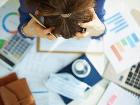Upper view of stressed middle age business woman at table