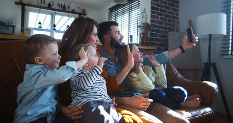 Happy young Caucasian family with three kids wave to friends talking during smartphone video call...