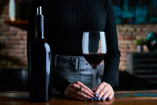 Woman in black shirt and grey skirt tasting red wine. Close up image of woman holding wine glass and wine bottle.