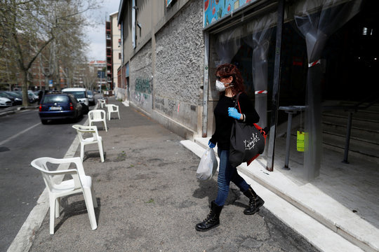 Italian chef Laura Carrera, 37 leaves the market wearing a protective mask and gloves as the spread of coronavirus disease (COVID-19) continues, in Rome