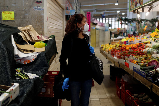 Italian chef Laura Carrera, 37, walks in a market wearing a protective mask and gloves as the spread of coronavirus disease (COVID-19) continues, in Rome