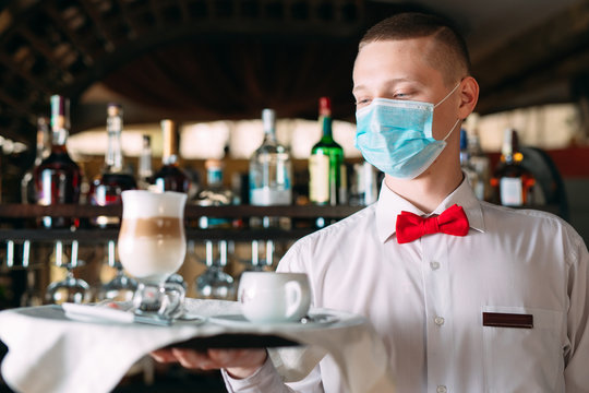 A European-looking waiter in a medical mask serves Latte coffee.