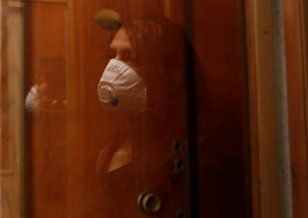 Italian chef Laura Carrera, 37, is reflected on glass of the elevator wearing face mask as the spread of coronavirus disease (COVID-19) continues, in Rome