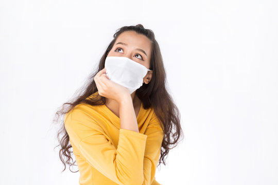 Young Worry Asian woman wearing hygienic mask to prevent infection corona virus Air pollution pm2.5 she wearing a yellow sweater shoot in shot isolated on white background