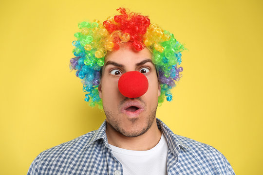 Funny man with clown nose and rainbow wig on yellow background. April fool's day