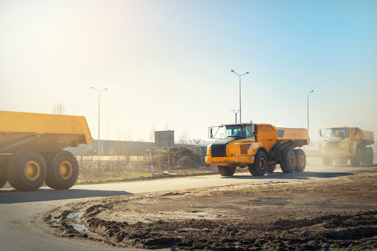 Many big articulated heavy industrial yellow dumper trucks driving on new highway road construction site on sunny day with blue sky background. Construction equipment machinery working on open pit