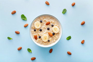 Bowl with tasty sweet oatmeal on color background Fotomurales