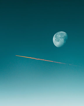 Moon and vapor trail in sky