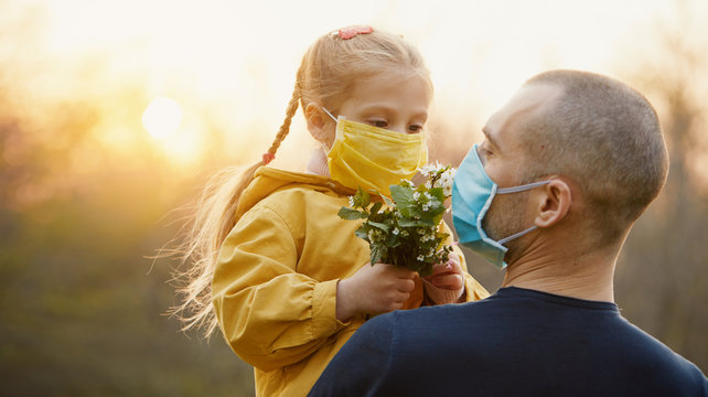 Family protection. A young father hugs his little girl daughter in the spring garden outdoors. Protective masks on faces from coronavirus infection