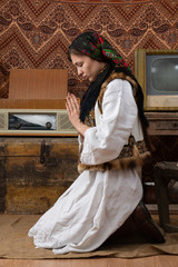 Young ukrainian girl in national clothes kneeling among old vintage retro room and praying