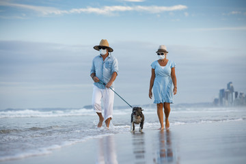 a couple with medical masks walking an english blue staffy dog, seaside on a beautiful beach....