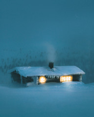 Exterior of illuminated snow covered cabin