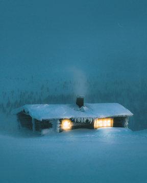 Exterior of illuminated snow covered cabin