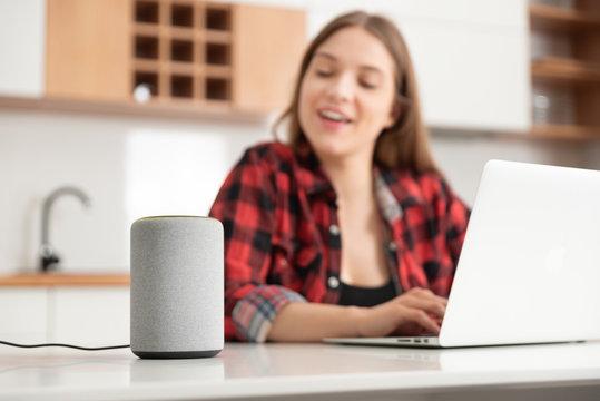 Woman talking to smart speaker. Smart home.