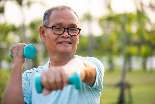 Asian old man doing physical exercise outdoor with dumbbells. Be healthy and strong, work on the muscles. Senior healthcare and sport concept.