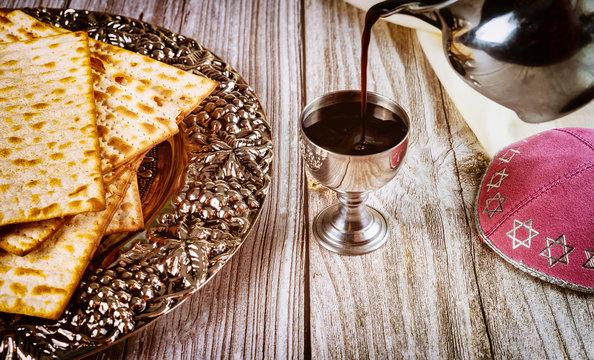 Kosher kiddush, matza and kippa on wooden background.