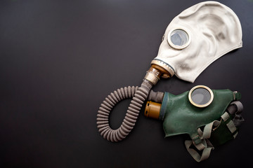 Obraz Codependent relationship, negative emotions, hazardous affair and toxic love concept with two gas masks connected on the same hose to represent codependency isolated on dark background with copy space - fototapety do salonu