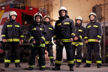 Six professional firefighters posing together. Firefighters wearing uniforms and protective helmets. Firetruck in the background.