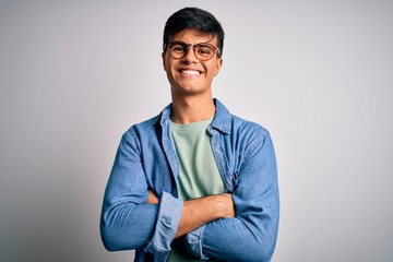 Fototapeta Young handsome man wearing casual shirt and glasses over isolated white background happy face smiling with crossed arms looking at the camera. Positive person.