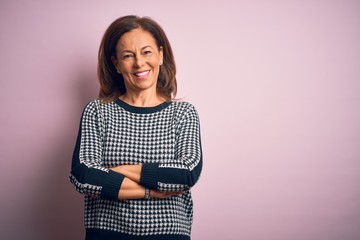 Wall Mural - Middle age beautiful woman wearing casual sweater standing over isolated pink background happy face smiling with crossed arms looking at the camera. Positive person.