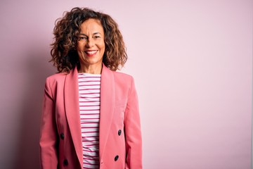 Middle age beautiful businesswoman wearing elegant jacket over isolated pink background with a...
