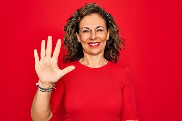 Wall Mural - Middle age senior brunette woman wearing casual t-shirt standing over red background showing and pointing up with fingers number five while smiling confident and happy.