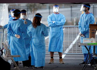 Medical students and physician assistants from Touro University Nevada wait to screen people in a temporary parking lot with spaces marked for social distancing in Las Vegas