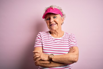 Senior beautiful sporty woman wearing sport cap standing over isolated pink background happy face smiling with crossed arms looking at the camera. Positive person.