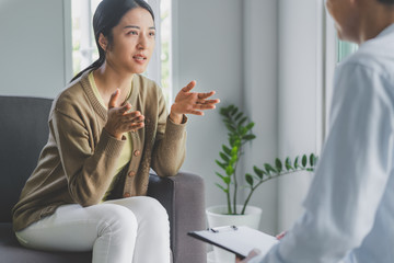 mental health treatment concept. Stressed asian patient talking with personal psychologist in therapist session have a burnout in work at clinic in office room.