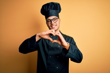 Young brazilian chef man wearing cooker uniform and hat over isolated yellow background smiling in love doing heart symbol shape with hands. Romantic concept.