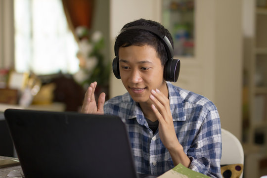 Young asian man talking on laptop camera to communicate with foreign tuitor learning language through online class at home.