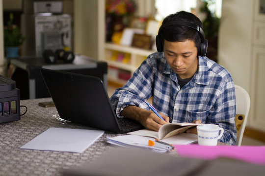 Young Asian man student study online class at home with serious face while looking at laptop and writing a short note.